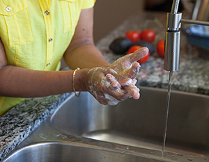 Closeup of hands being washed with soap and water.